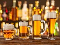 杯与酒吧的低度黄啤酒在背景 免版税库存图片