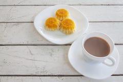 杯与金蛋黄螺纹蛋糕的热的可可粉在白色木桌上 免版税库存照片