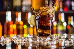 杯与飞溅的可乐饮料在酒吧柜台 免版税库存图片