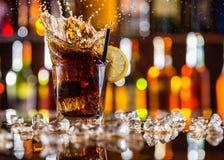 杯与飞溅的可乐饮料在酒吧柜台 免版税图库摄影