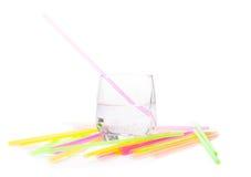 杯与鸡尾酒秸杆的水在白色 免版税库存照片