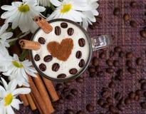 杯与�innamon和白花的热奶咖啡 免版税图库摄影