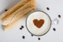 杯与�innamon和酥皮点心的热奶咖啡 库存图片
