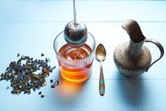 杯与水罐和茶叶,过滤器酿造的茶 免版税库存照片