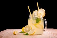杯与黄色秸杆的柠檬水与新鲜薄荷叶子和石灰、水多的柠檬和矿泉水在黑背景 免版税库存照片