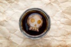 杯与头骨形状冰的可乐饮料 免版税库存照片