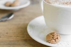 杯与biscotti的咖啡馆拿铁在木桌上 图库摄影