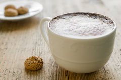 杯与biscotti的拿铁咖啡在木桌上 免版税库存照片