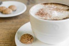 杯与biscotti的拿铁macchiato在木桌上 免版税图库摄影