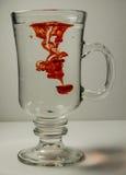 杯与RED丢弃的水 免版税库存照片