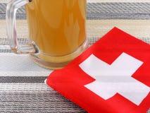 杯与suisse旗子的啤酒 库存图片