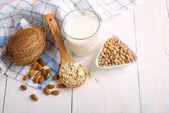 杯从坚果的素食主义者牛奶有在白色木桌上的各种各样的坚果的 乳糖自由产品,另外牛奶替代品,大豆,燕麦 免版税库存照片