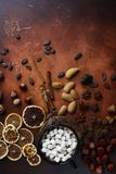 杯传统热巧克力或可可粉用蛋白软糖、桂香、坚果和香料在黑暗的石桌上 免版税库存照片