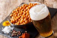 杯低度黄啤酒用快餐紧密烤被盐溶的鸡豆 免版税库存图片
