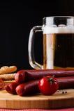 杯低度黄啤酒、肉香肠和蕃茄在木板 免版税库存照片