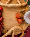 杯低度黄啤酒、肉香肠和蕃茄在木板 库存图片