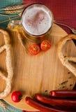 杯低度黄啤酒、肉香肠和蕃茄在木板 免版税图库摄影