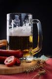 杯低度黄啤酒、肉香肠和蕃茄在木板 免版税库存图片