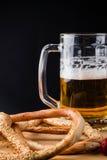 杯低度黄啤酒,在木板,背景的椒盐脆饼 免版税库存图片