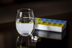 杯光滑的黑表面上的水和药片片剂 库存图片
