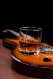 杯兰姆酒和琴拨在电吉他 免版税库存照片