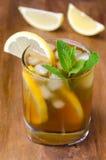 杯冰茶用柠檬和薄菏在木背景 免版税库存照片