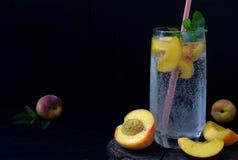 杯冷的自创桃子柠檬水或mojito鸡尾酒用薄菏在黑暗的背景 苏打饮料 复制空间 拍摄与 免版税图库摄影
