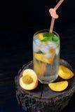杯冷的自创桃子柠檬水或mojito鸡尾酒用薄菏在黑暗的背景 苏打饮料 复制空间 拍摄与 图库摄影