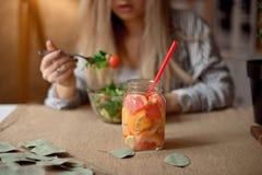 杯反对吃新鲜的沙拉的女孩的被弄脏的背景的柠檬水 图库摄影