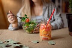 杯反对吃新鲜的沙拉的女孩的被弄脏的背景的柠檬水 免版税库存图片