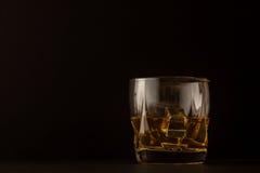 杯反对黑暗的背景的威士忌酒 库存照片
