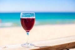 杯反对绿松石海的红葡萄酒 免版税图库摄影