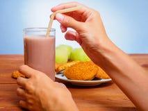 杯可可粉用麦甜饼 拿着管的妇女的手 库存图片