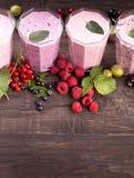 杯各种各样的新鲜的莓果圆滑的人 免版税库存照片