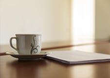 杯和堆在他的书桌上的纸 库存照片