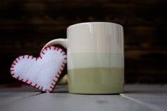 杯和心脏在木板 免版税图库摄影