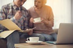 杯和笔记本在书桌上在资深领抚恤金者附近 免版税库存图片