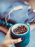 杯咖啡豆,手和温暖的毛衣,装饰用被带领的光,顶视图点 免版税库存图片
