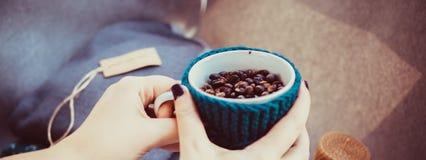 杯咖啡豆,手和温暖的毛衣,装饰用被带领的光,顶视图点 库存照片