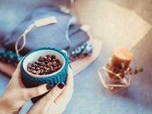 杯咖啡豆,手和温暖的毛衣,装饰用被带领的光,顶视图点 免版税图库摄影
