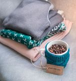 杯咖啡豆,温暖的毛衣,装饰用被带领的光,侧视图点 免版税库存图片