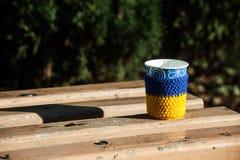 杯咖啡长木凳报道的雪mornimg黄色蓝色热编织 图库摄影