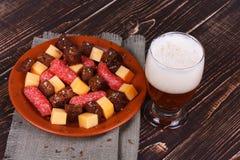 杯啤酒、乳酪和熏制的香肠 免版税图库摄影
