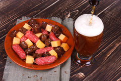 杯啤酒、乳酪和熏制的香肠 图库摄影