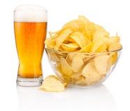杯啤酒和土豆片在白色隔绝的玻璃碗 免版税库存图片