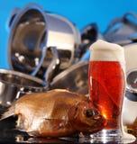 杯啤酒和干鱼,被洗涤的干净的平底锅 库存照片