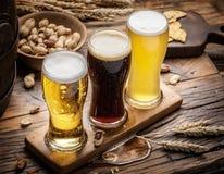 杯啤酒和快餐在木桌上 库存图片