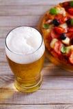 杯啤酒和比萨在木桌上 啤酒和食物概念 侥幸 免版税库存图片
