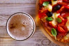 杯啤酒和比萨在木桌上 啤酒和食物概念 侥幸 免版税图库摄影