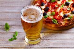 杯啤酒和比萨在木桌上 啤酒和食物概念 侥幸 免版税库存照片